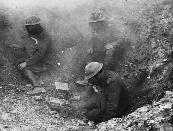 Three members of the British Army Signal Service, wearing gas masks, in a trench on the Western Front, a typical forward Signal Post
