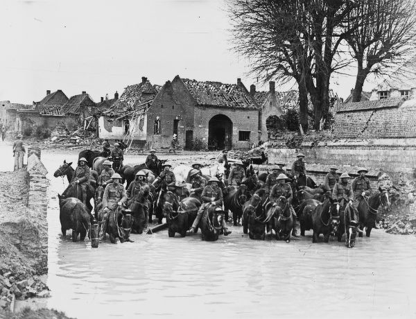 British cavalry standing in water on horses in a ruined town in France on the British front during World War I in 1917