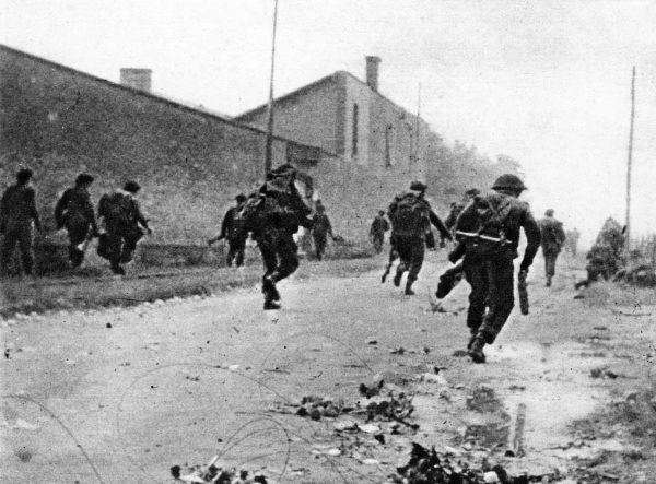 Photograph showing British Commando troops sprinting forward to attack German positions in Normandy, France, during June 1944. This image was taken shortly after the Allied invasion on 'D-Day', 6th June