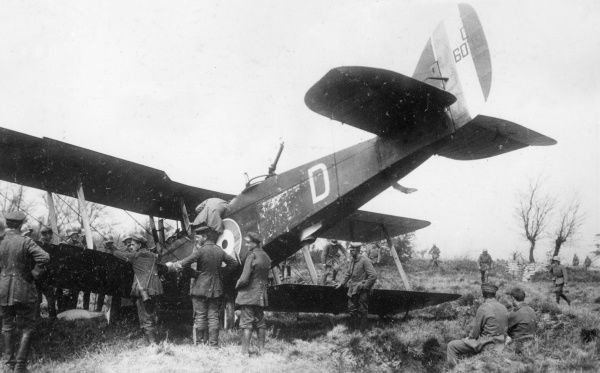 A British DH9 De Havilland biplane which has made a forced landing on the Western Front in France during the First World War. Seen here surrounded by German troops. Date: 1918