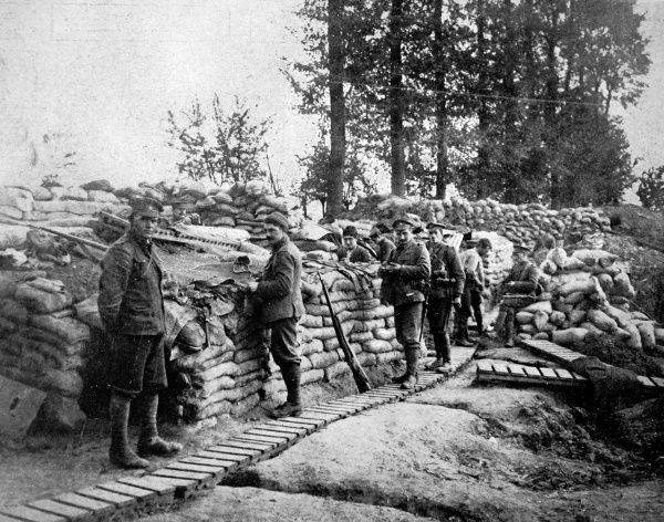 British soldiers in a firing-line trench with rifles leaning against sandbags and duckboard pathways
