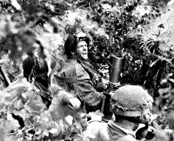 Photograph showing men of the British First Airborne Division using a 3-inch mortar in one of the woods surrounding Arnhem, in Holland, September 1944