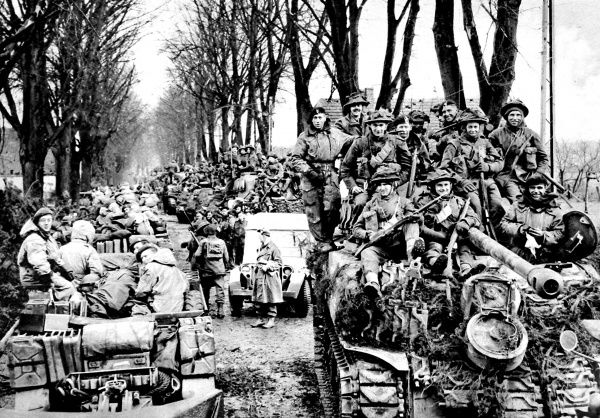 Photograph showing British infantry riding on Sherman tanks towards the Reichswald area, Germany, February 1945. On the left of the image anti-tank guns and their crews can be seen