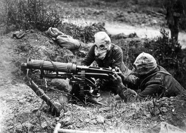 Two British machine gunners near Ovillers during the Battle of the Somme, northern France, during the First World War. They are using a Vickers Gun and wearing their gas helmets. Date: July 1916