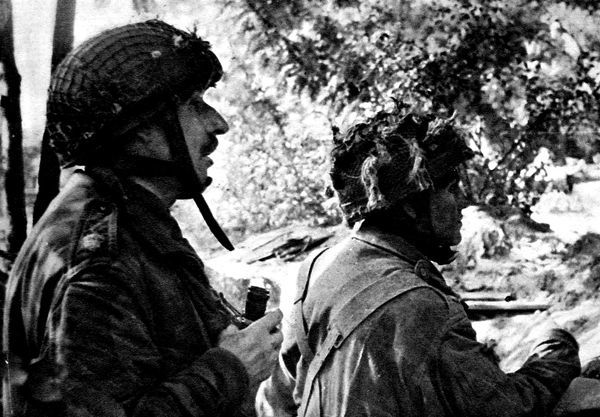 Photograph showing a Major (on left) and Lieutenant of the British First Airborne Division in the woods near Arnhem, Holland, September 1944. The original caption for this image said that the Lieutenant was giving orders to a machine-gun crew