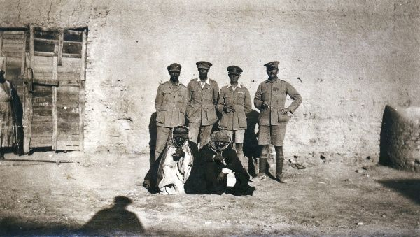 Four British officers and two Arab men outside a building, somewhere in the Middle East
