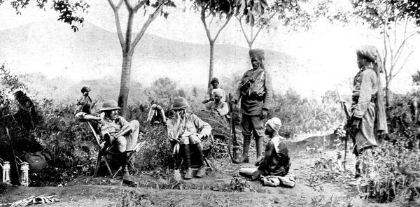 Photograph showing General Hannyngton and his intelligence officer (seated in chairs) interrogating an enemy porter (seated on floor) in German East Africa, 1916. Two Indian sepoys stand guard by the prisoner