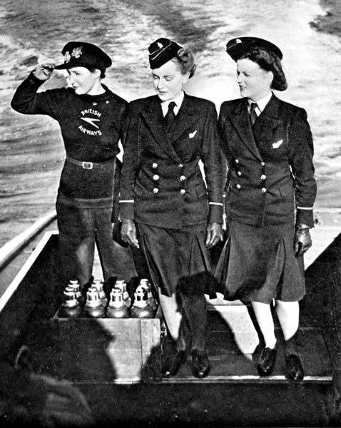 Photograph showing two stewardesses (on right) of the British Overseas Airways, in the stern of a motor-launch, heading out to join a waiting flying-boat, 1943