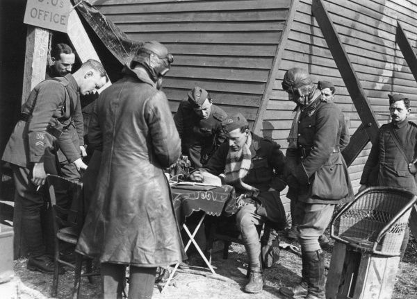 British pilots of No. 15 Squadron handing in reports after flying over enemy lines, near Albert, northern France, during the First World War. Major H V Stammers (OC, Officer Commanding) is sitting at the table; the Air Mechanic on the right is AMF Jackson