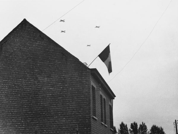 British planes carrying Airborne troops for the landing in Holland during World War II, pass over the Belgian flag, symbol of the liberation of the Belgian people