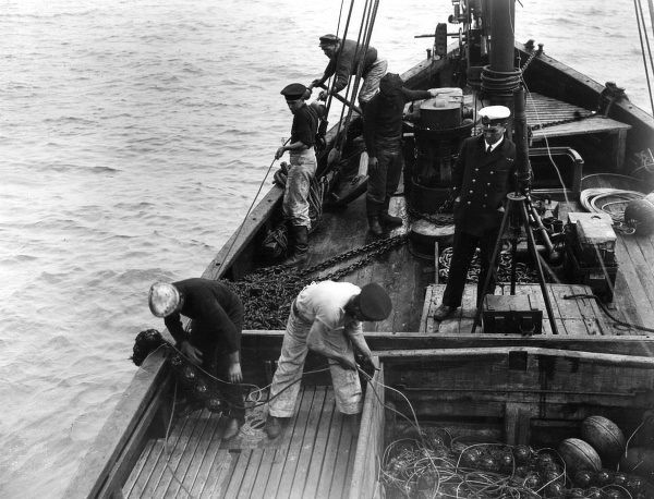 British sailors laying anti-submarine nets from a drifter, lowering the nets and floats over the side, during the First World War. Date: 1914-1918