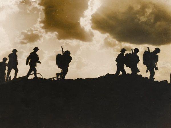 Men of the East Yorkshire regiment, silhouetted, make their way around shell craters at Frezenberg, during the Third Battle of Ypres