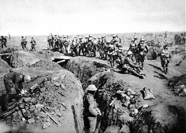 A party of British soldiers, moving off for an attack, are pictured crossing a trench-bridge, September 1916