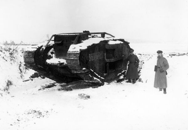 "A British tank, with the name ""Barbarian II"" painted on its side, in the snow on the Western Front during the First World War. Two German soldiers stand alongside it. Date: 28 December 1917"