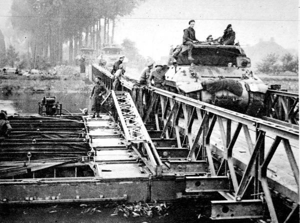 Photograph showing British tanks and self-propelled guns crossing a Bailey bridge, Holland, 1944. This bridge had been built by British engineers over a canal during Operation 'Market Garden', as 30 Corps rushed towards Arnhem