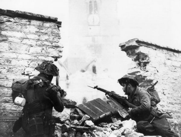 British troops, wary of German snipers, move cautiously behind a ruined wall in St. Mauvieu, France. Date: 6 June 1944