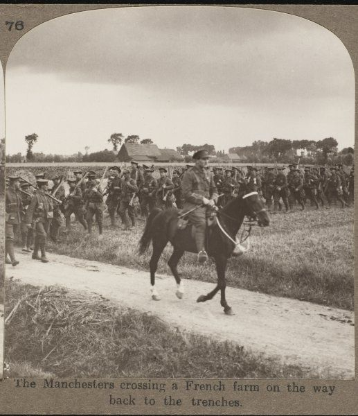 Soldiers of the Manchester Regiment crossing a French farm on the way back to the trenches
