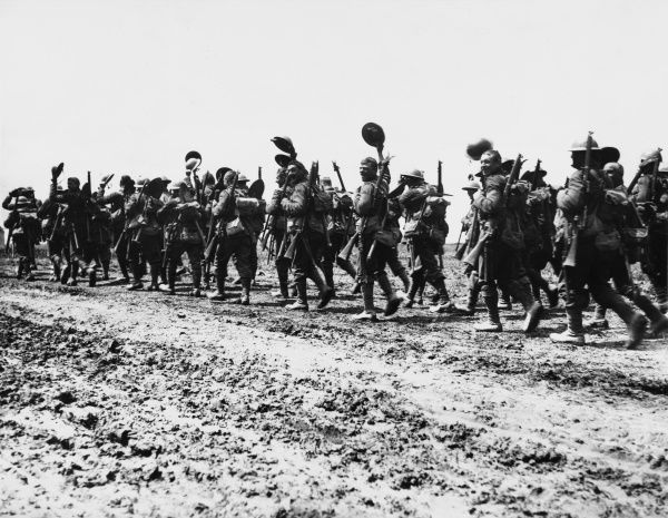 British troops, possibly from the Worcestershire Regiment, march along the Acheux Road, happily waving their helmets at the photographer as they head for the front line trenches a few days before the commencement of the Battle of the Somme
