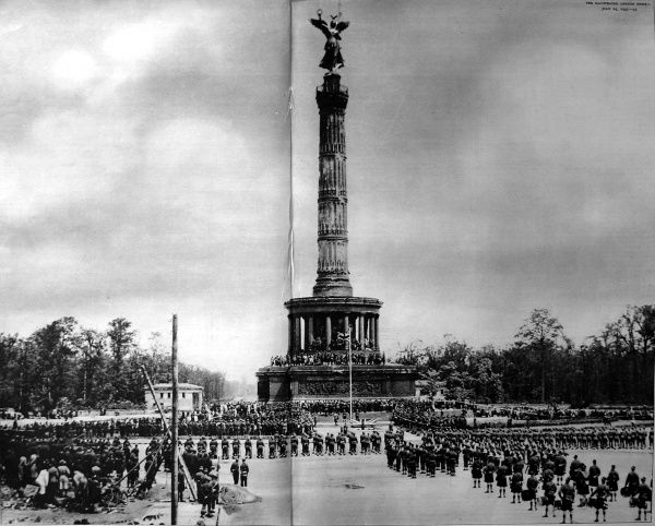 Photograph showing British troops, of the Seventh Armoured Division, parading in front of the German victory column in Konigsplatz, Berlin, 1945. Date: 14/07/1945