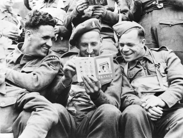 British troops reading French guide before embarking for the D Day Landings during the Second World War in 1944