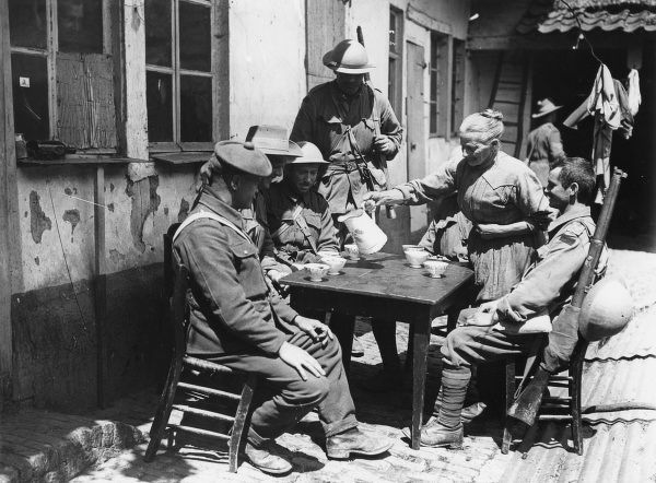 British troops relaxing at Croix du Bac, near Armentieres, northern France, during the First World War. An elderly Frenchwoman is serving them with coffee in china cups. Date: May 1916