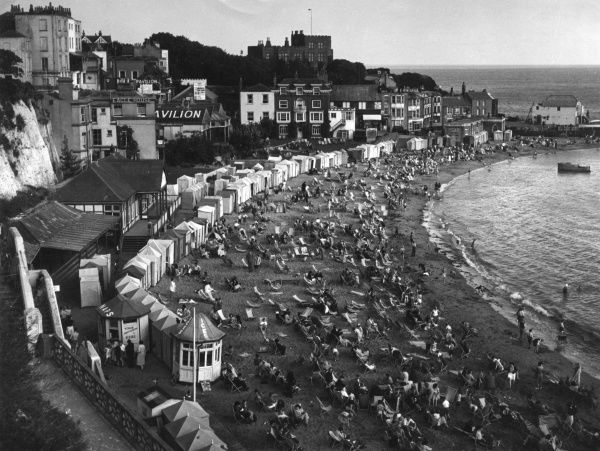 An elevated view of the beach at Broadstairs in Kent, crowded with holidaymakers, deckchairs and bathing huts. Date: 1940s