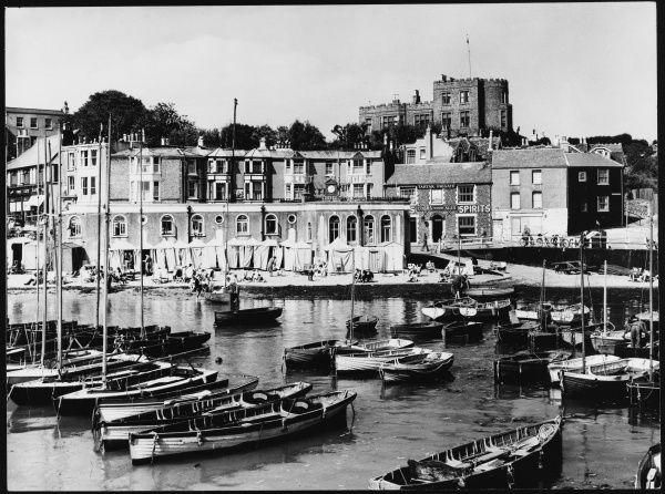 General view of Broadstairs looking inland, showing the harbour with fishing boats; bathing huts behind and Bleak House, former residence of Charles Dickens, on the hill. Date: 1950s