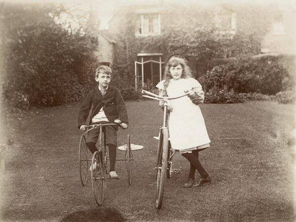 A brother and sister pose in their attractive back garden with their cycles. The boy sits on a tricycle and the girl stand propped up against her bicycle