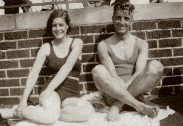 A brother and sister on holiday, leaning against a wall in their swimsuits. Date: circa 1930s