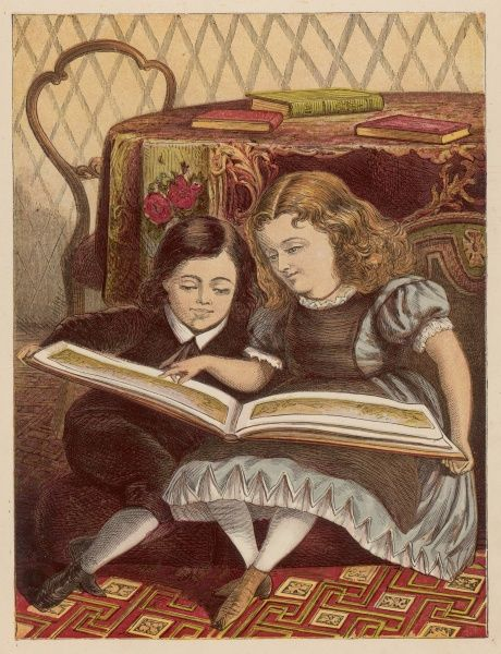 A girl and her brother sit on the carpeted floor reading a very large picture book