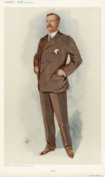 John McAusland Denny wears a brown suit with a short double-breasted jacket & trousers with a front crease, brown boots & an all round collar & tie
