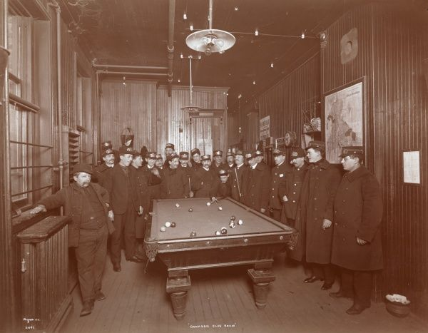 Canarsie Club Room. Men in uniform posed behind a pool table in the Brooklyn Rapid Transit's Canarsie Clubhouse billiard room