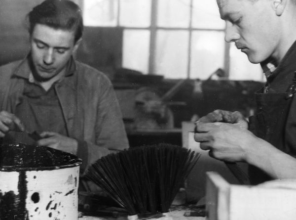 Young brushmakers knotting bristles after dipping them in pitch, Leicestershire, England. Date: 1950s