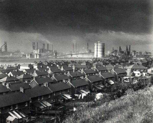View of the BSC (British Steel Corporation) works in Port Talbot, West Glamorgan, South Wales, with rows of houses in the foreground. A dark cloud of pollution can be seen hanging above the town, with smoke from chimneys adding to it