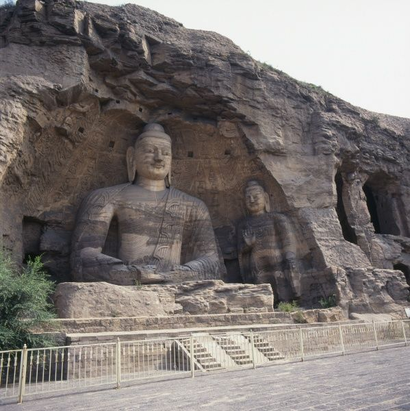 Two Buddha statues of varying size carved from the rock at the Yungang (Cloud Ridge) Caves or Grottoes in Datong, Shanxi Province, in the People's Republic of China