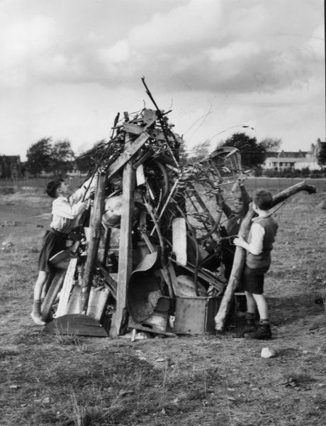 Gleeful boys building a huge bonfire of household rubbish! Date: 1950s