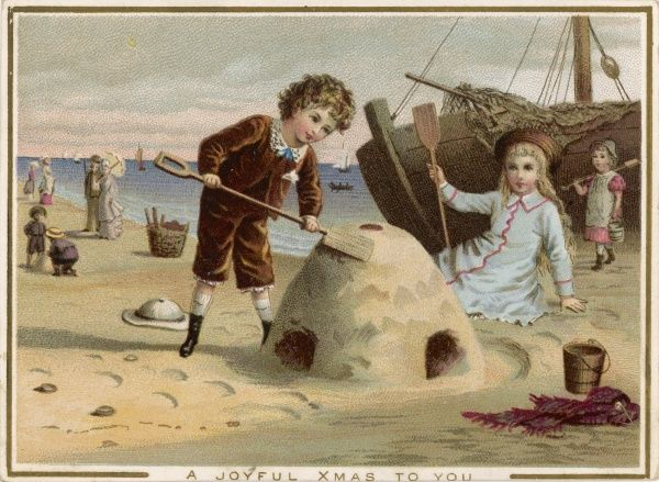 A boy and a girl, dressed in their best clothes, build a castle on a sandy beach