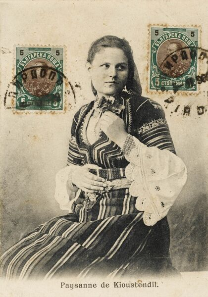 Bulgarian Beauty in National Costume. Note the fine (and wide) patterned cuffs on her white blouse. She is from Kyustendil (Velbazhd), a town in the far west of Bulgaria, the capital of Kyustendil Province