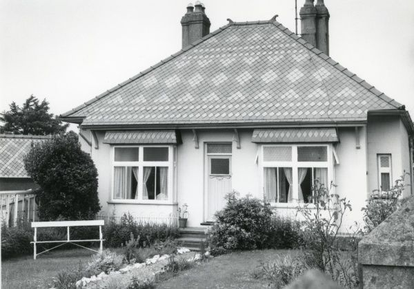 A bungalow with an elaborately patterned slate roof, somewhere in North Wales where the slate is quarried