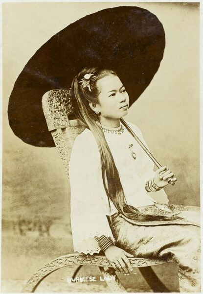 A pretty girl from Burma (modern Myanmar), seated in an elegant and decorative carved chair and holding a dark parasol. She has long dark hair and many metal bracelets on each arm