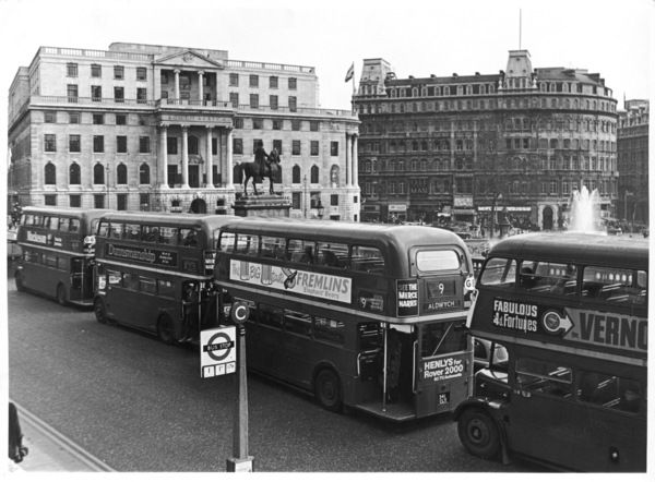 Four 'Routemaster' London buses in a queue on the National Gallery side of Trafalgar Square, with the South African embassy in the background