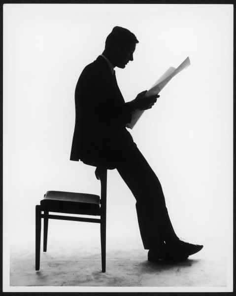 A silhouette of a businessman leaning against a chair reading a newspaper