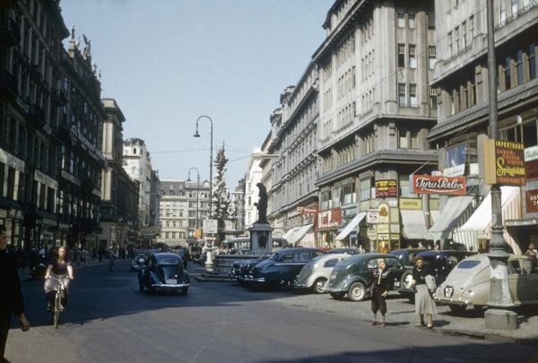 View of a busy high street in Vienna, Austria, with traffic, parked cars and people out shopping. Date: 1953