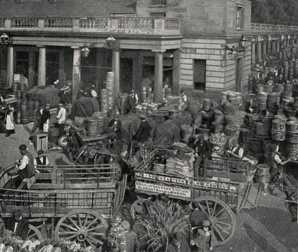 A busy scene outside Covent Garden Market, London. Horse-drawn carts are being loaded up with baskets of fruit and flowers