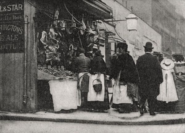 Women turning over scraps and shreds of beef and mutton at a butcher's stall in the East End of London