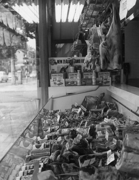 The window display of a butcher's shop which has various cuts of meat as well as a selection of sausages and tinned goods