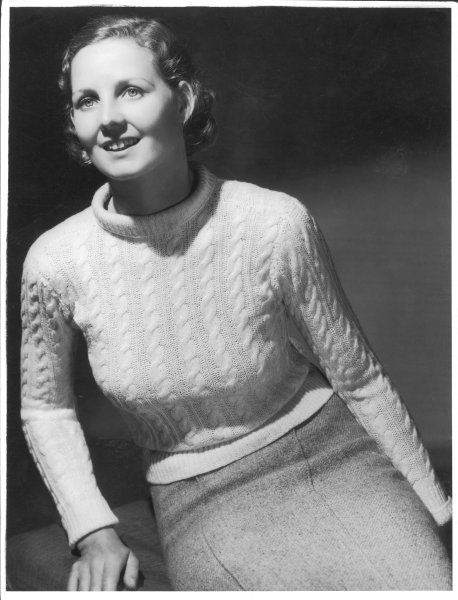 A hand-knitted jumper in a cable stitch with cuffs & a roll collar. Here it is worn with a woollen skirt