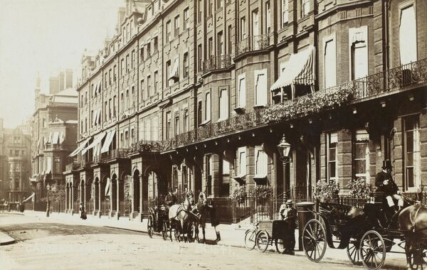 Cadogan Square - the jewel in the crown of the Cadogan Estate, Chelsea, London. A baker delivers the morning bread from a tricycle with a large wicker basket attached. Carriages await their wealthy passengers at the pavement's edge