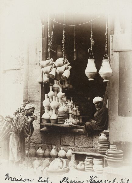 A pot seller in Cairo, Egypt with his wide selection of pottery in varied shapes and sizes. He sits in the open entrance to his shop and talks to a passing fresh water carrier / seller