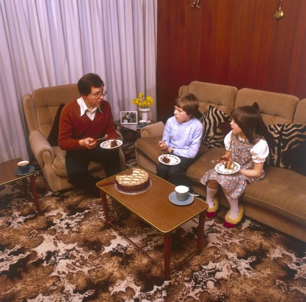 Children scoffing a large chocolate cake with their Dad on a hideous chocolate coloured sofa! Date: 1981